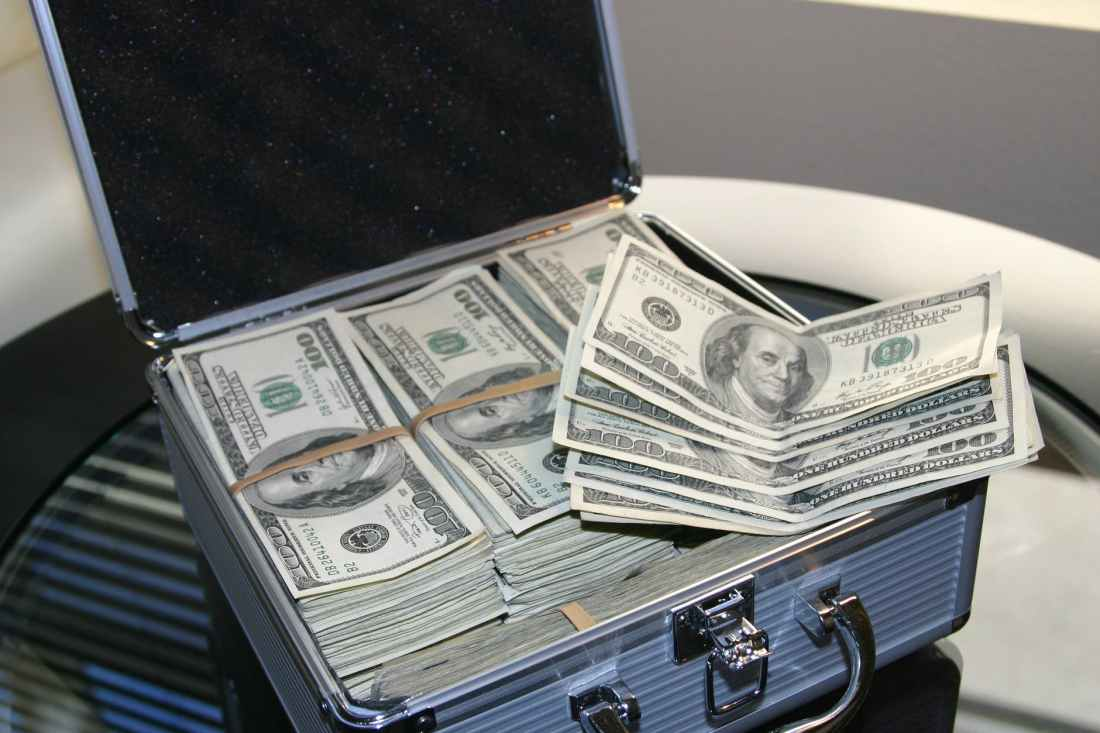 piles of u s dollar bills on silver and white suitcase
