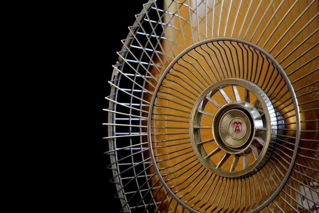close up photography of gray stainless steel fan turned on surrounded by dark background