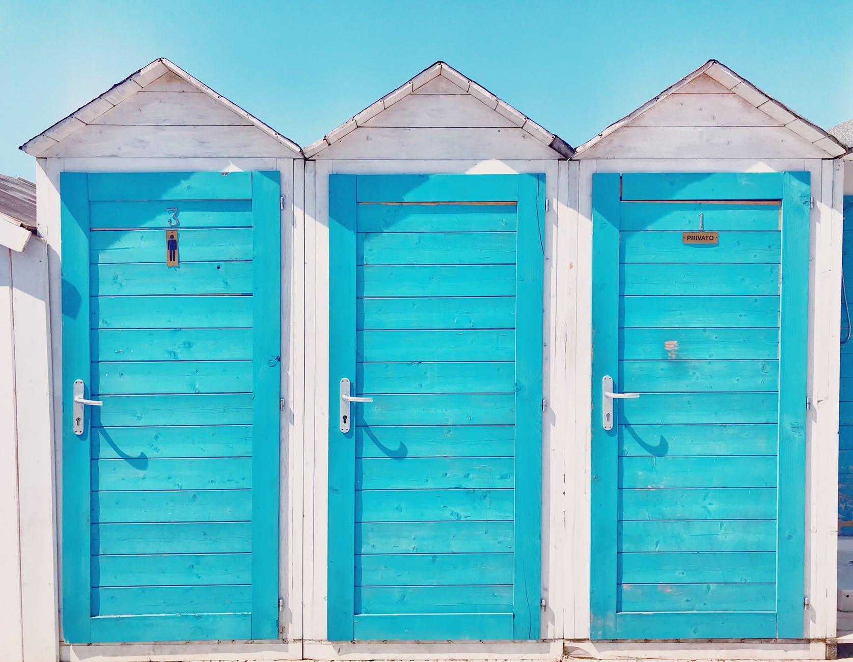 photo of three wooden toilets