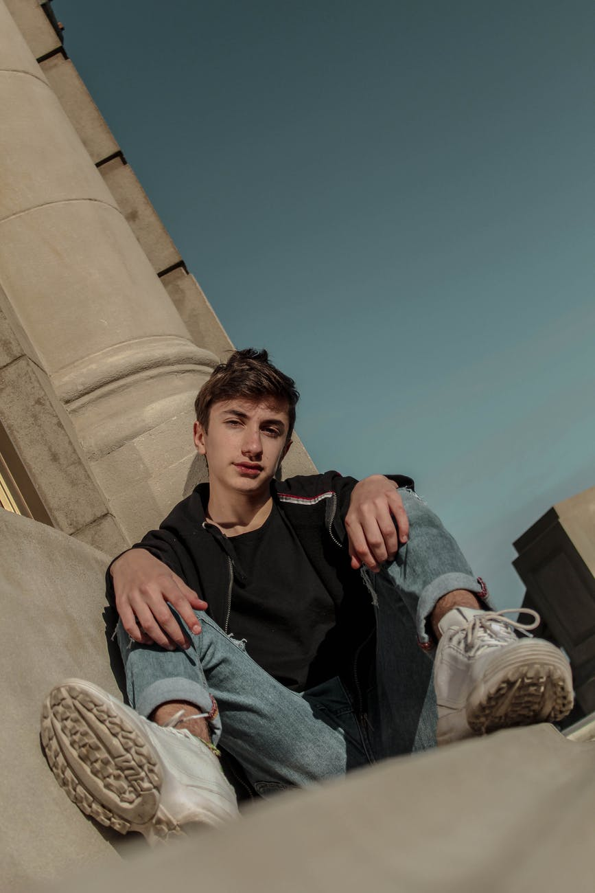 photo of teenage boy sitting beside gray pillar