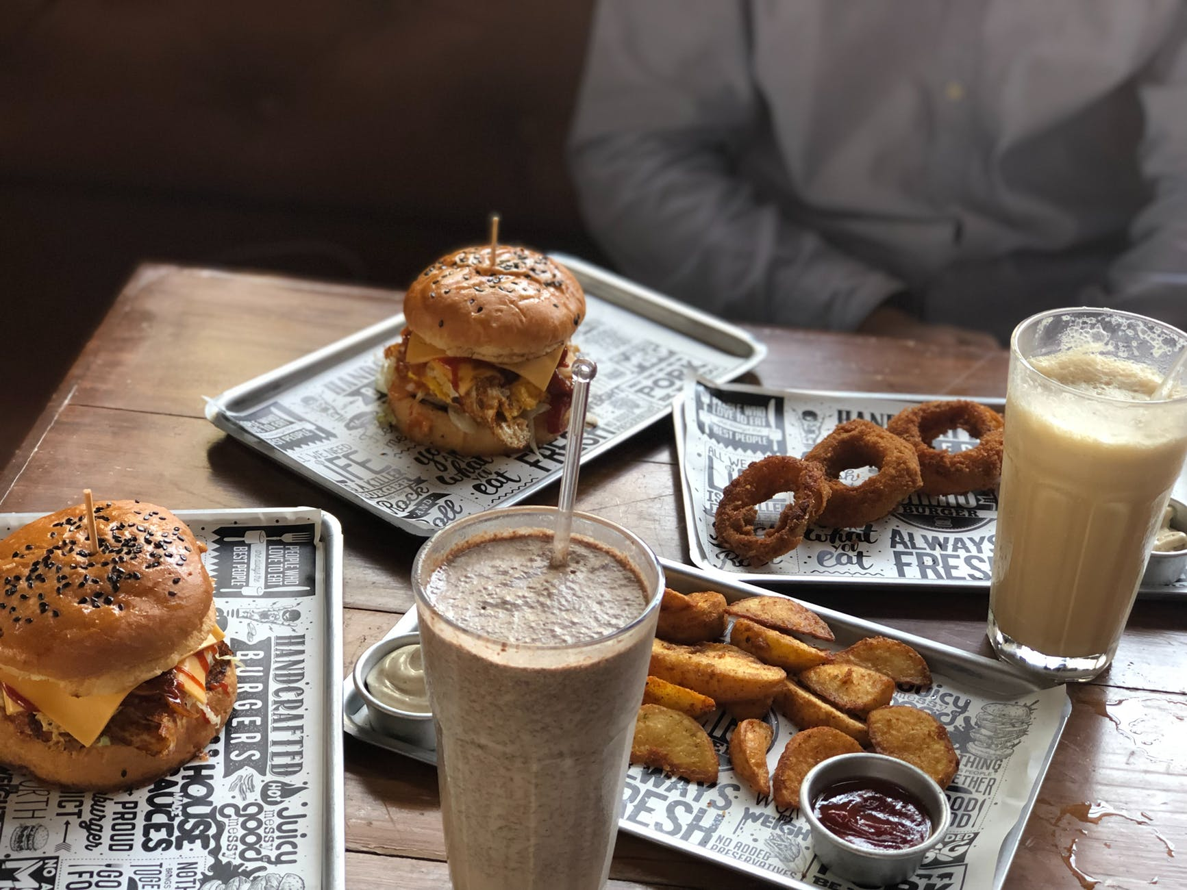 two milk shakes burgers fried onion rings and wedge potatoes on the table