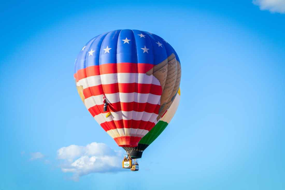 white red and blue hot air balloon flying