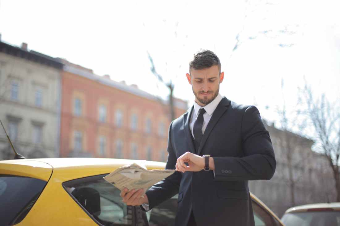 man in black suit standing beside the yellow car