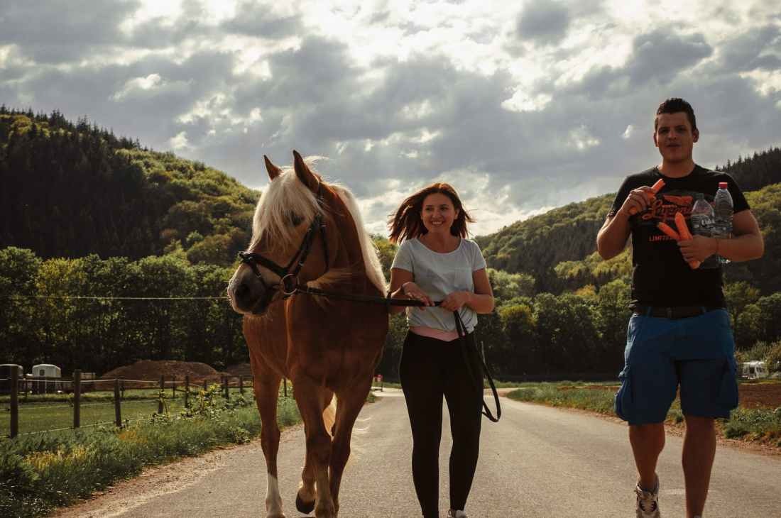 woman walking between horse and a man