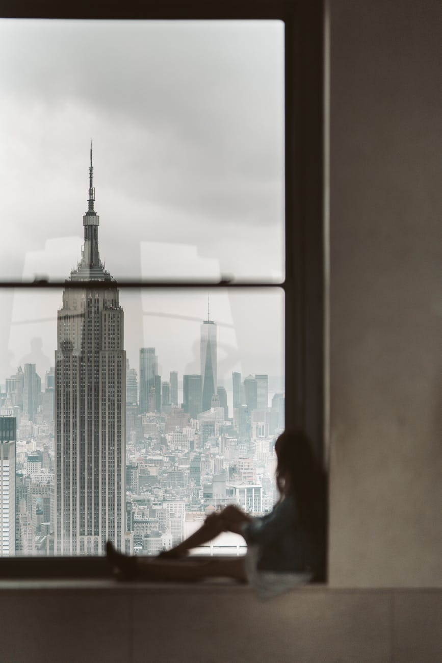 woman sitting at window sill looking out the window at new york city