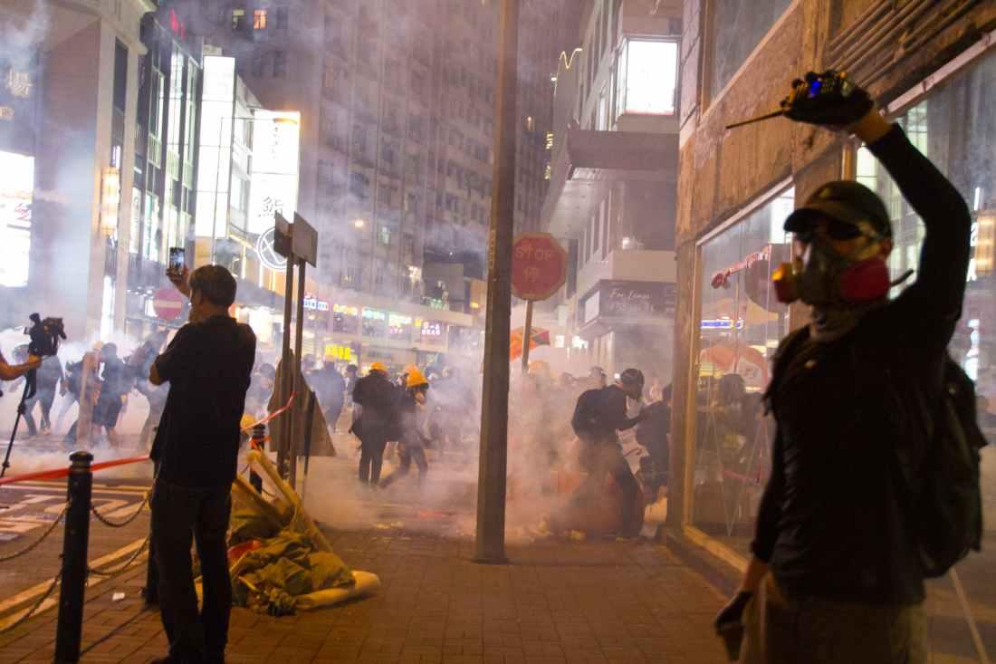 man wearing gas mask standing beside store facade