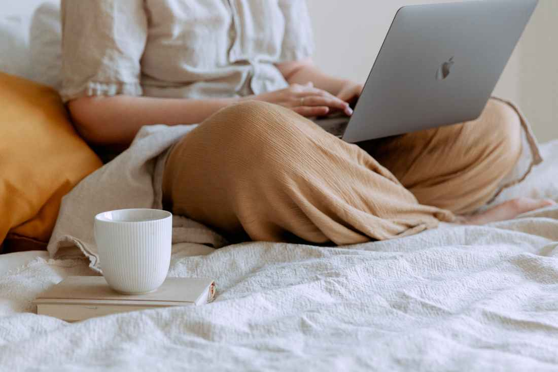 crop woman lounging with laptop and cup of coffee on bed at home
