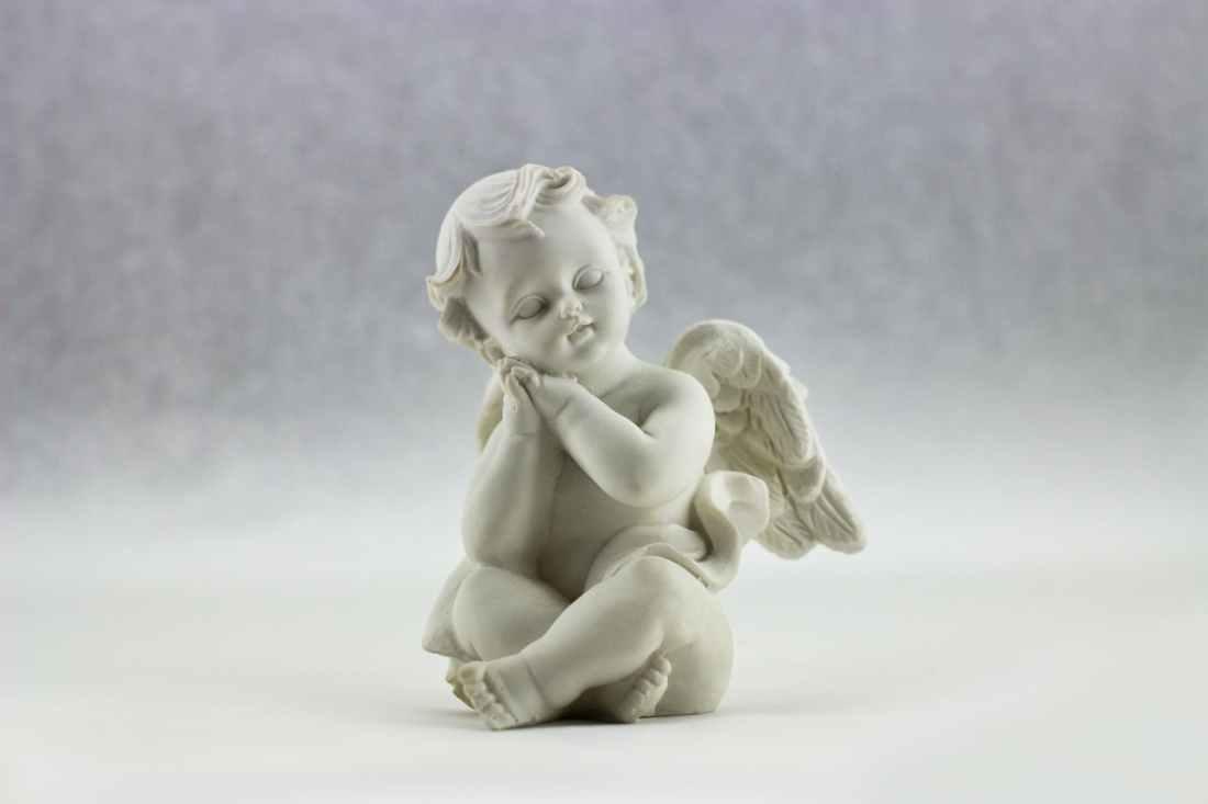 white ceramic figurine of angel illustration