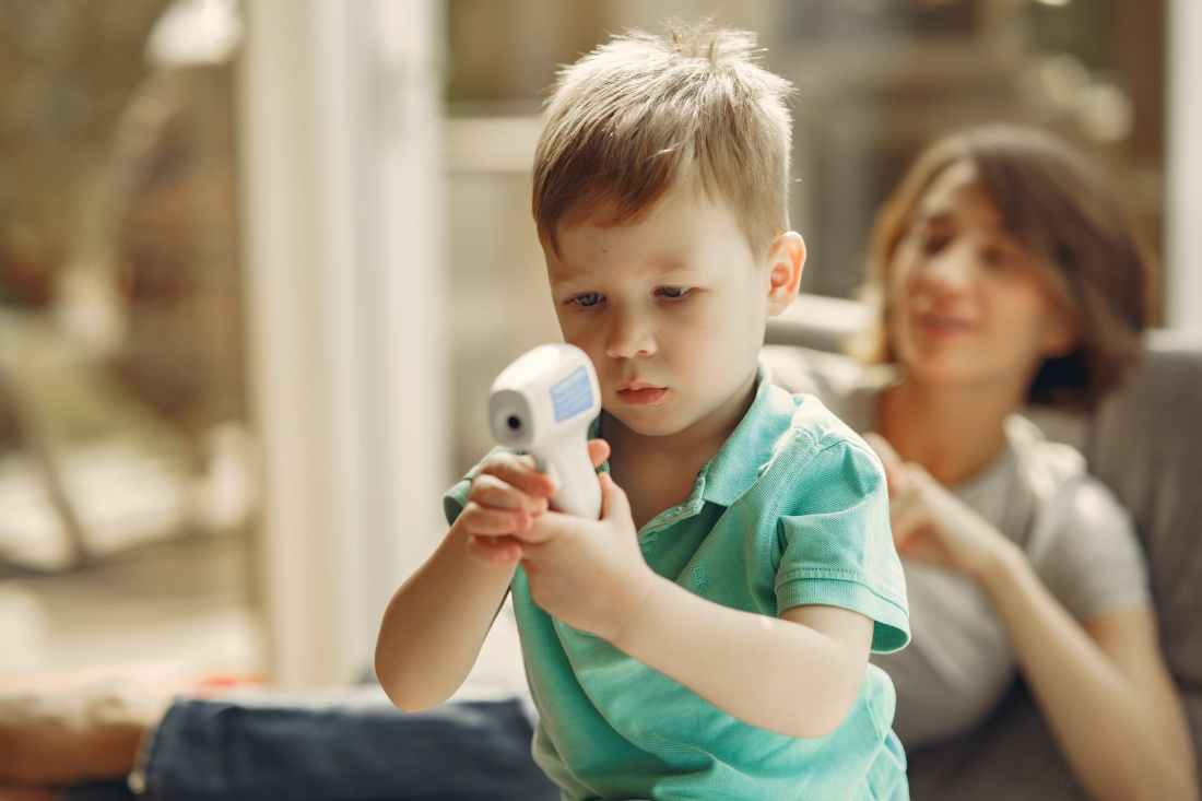 curious little boy watching infrared thermometer standing behind mother