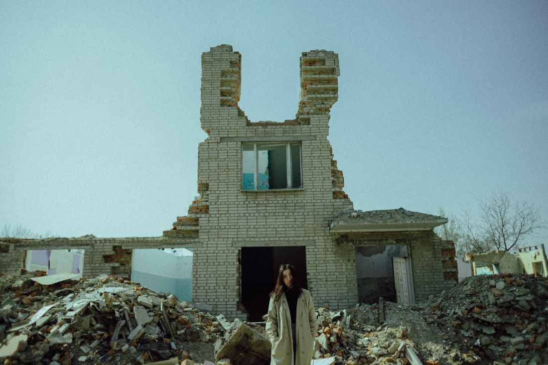 woman standing near a demolished concrete building